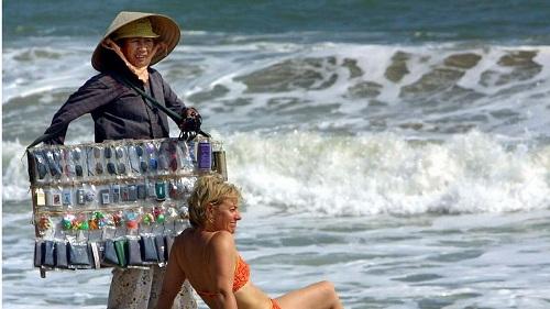 Một người bán hàng rong chào mời du khách mua kính râm tại Nha Trang. Ảnh:AFP.